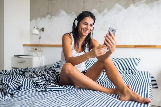 Młoda atrakcyjna kobieta siedzi na łóżku w piżamie, uśmiecha się w sypialni, radosne emocje, budzi się rano, śmiech, seksowna, chuda, słuchanie muzyki na słuchawkach, używanie smartfona, robienie zdjęć selfie