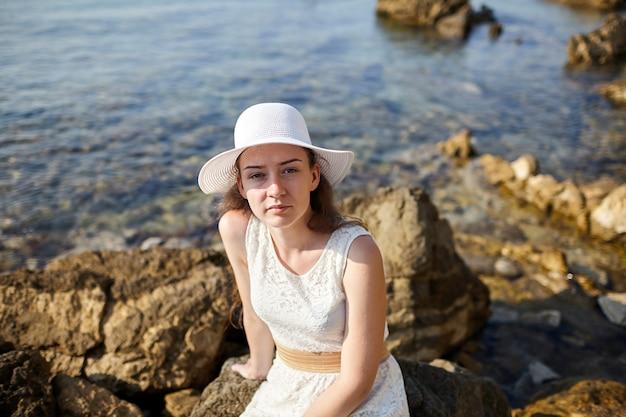 Młoda atrakcyjna kobieta siedzi na skałach w białej sukni i kapeluszu na wodzie morskiej