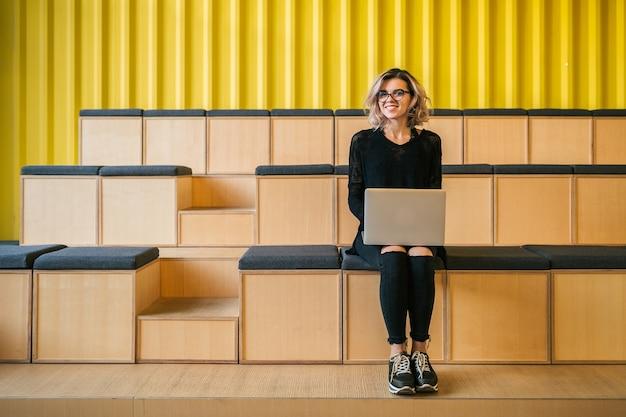 Młoda atrakcyjna kobieta siedzi w sali wykładowej, pracuje na laptopie, w okularach, nowoczesne audytorium, edukacja studencka online, freelancer, uśmiechnięta, nastoletni startup, patrząc w kamerę, szczęśliwa