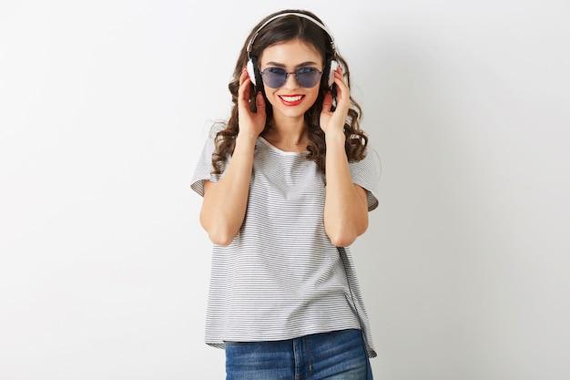 Młoda atrakcyjna kobieta słuchania muzyki na słuchawkach, noszenie okularów przeciwsłonecznych, na białym tle