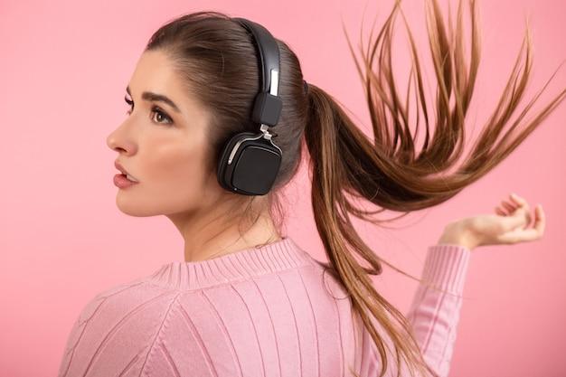 Młoda atrakcyjna kobieta słuchanie muzyki w słuchawkach bezprzewodowych na sobie różowy sweter uśmiechnięty szczęśliwy pozytywny nastrój pozowanie na różowym tle na białym tle macha długimi włosami ogonem