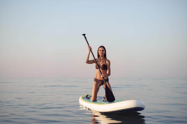 Młoda atrakcyjna kobieta stojąca na desce wiosłowej o wschodzie słońca