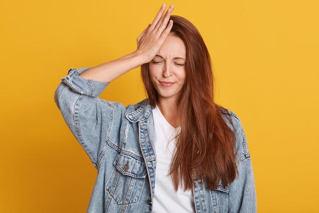 Młoda atrakcyjna kobieta stojąca z zamkniętymi oczami i trzymająca rękę na czole, pamięta o czymś ważnym
