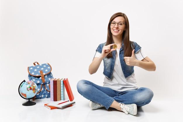 Młoda atrakcyjna kobieta studentka w okularach trzymająca bitcoina pokazująca tumb up siedzącego w pobliżu kuli ziemskiej, plecaka, podręczników szkolnych na białym tle