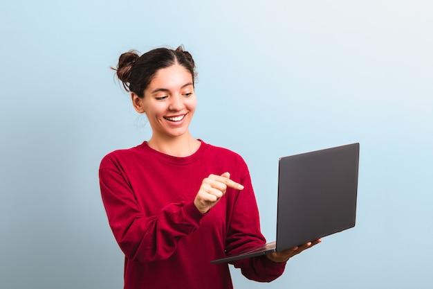 Młoda atrakcyjna kobieta studentka z śmieszną twarzą trzymając laptopa i wskazując na to applaying dla rejestracji na uniwersytet lub college