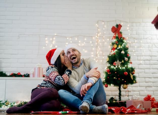 Młoda atrakcyjna kobieta szepcząc do swojego przystojnego uśmiechniętego mężczyzny, siedząc na podłodze z czapkami mikołaja na boże narodzenie w domu.