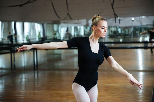 Młoda atrakcyjna kobieta tańczy w klasie baletowej