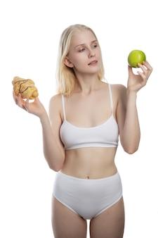 Młoda atrakcyjna kobieta trzyma jabłko i ciasto w ręce w zdrowej kontra smaczne