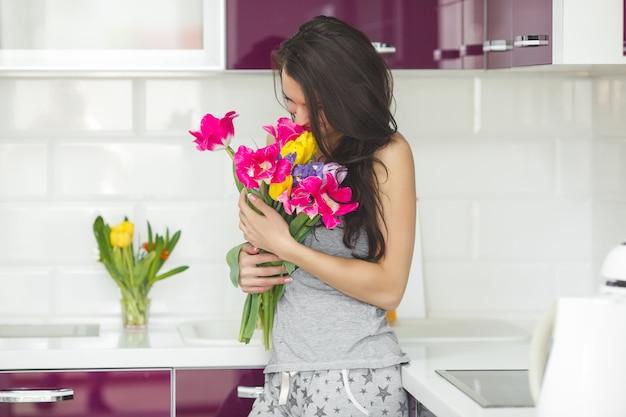 Młoda atrakcyjna kobieta trzyma kwiaty. dama w kuchni z tulipanami. gospodyni rano stojąc w domowej kuchni.