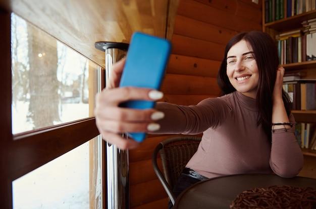 Młoda atrakcyjna kobieta trzyma smartfona i uśmiecha się, robiąc selfie, siedząc w kawiarni na tle drewnianej ściany i półek z książkami