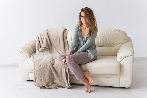 Młoda atrakcyjna kobieta ubrana w piękną kolorową piżamę udając modela w swoim salonie