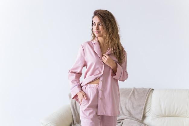 Młoda atrakcyjna kobieta ubrana w piękną kolorową piżamę udającą modelu w swoim salonie.