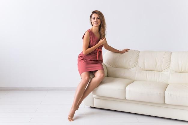 Młoda atrakcyjna kobieta ubrana w piękną sukienkę domu siedzi na kanapie w swoim salonie