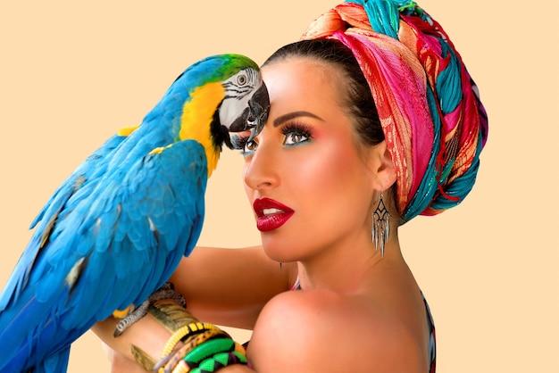 Młoda atrakcyjna kobieta w afrykańskim stylu z papugą ara na dłoni na kolorowym tle