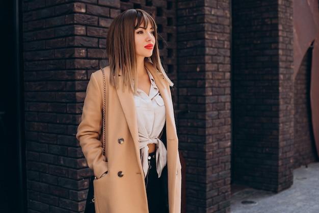 Młoda atrakcyjna kobieta w beżowym płaszczu pozuje na ulicy