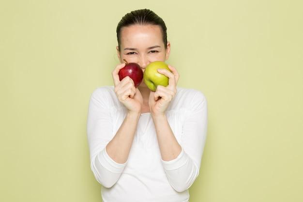 Młoda atrakcyjna kobieta w białej koszuli uśmiecha się i trzyma jabłka zielone i czerwone