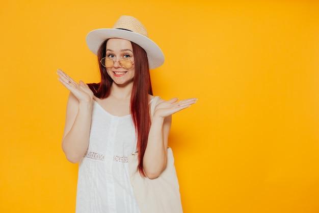 Młoda atrakcyjna kobieta w białym kapeluszu i białej letniej sukience z torby na zakupy ekologiczne uśmiecha się. copyspace.
