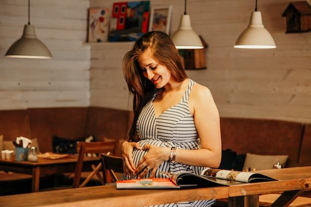 Młoda atrakcyjna kobieta w ciąży. kobieta w ciąży chłodzi w kawiarni. koncepcja życia miasta.
