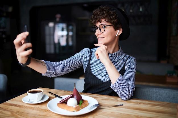 Młoda atrakcyjna kobieta w eleganckiej odzieży codziennej i kapeluszu co selfie podczas relaksu w kawiarni i deser