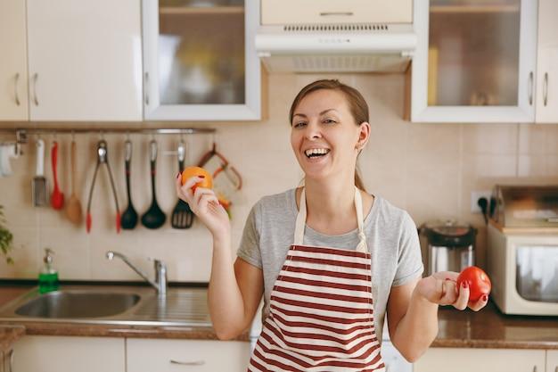Młoda atrakcyjna kobieta w fartuchu postanawia wybrać w kuchni pomidora w kolorze czerwonym lub żółtym. koncepcja diety. zdrowy tryb życia. gotowanie w domu. przygotuj jedzenie.