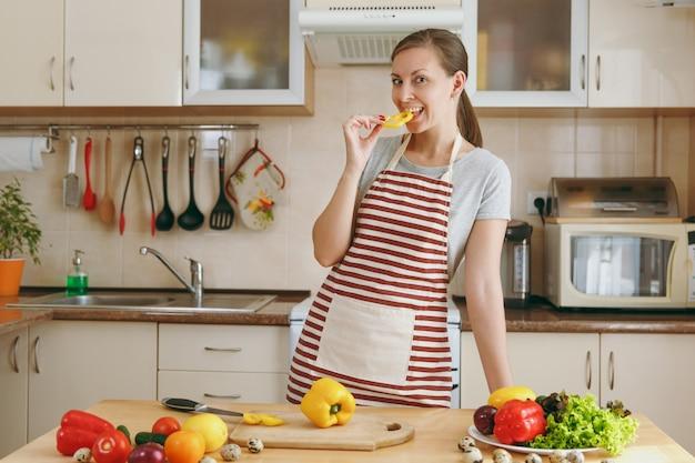 Młoda atrakcyjna kobieta w fartuchu smakuje w kuchni żółtą paprykę. koncepcja diety. zdrowy tryb życia. gotowanie w domu. przygotuj jedzenie.