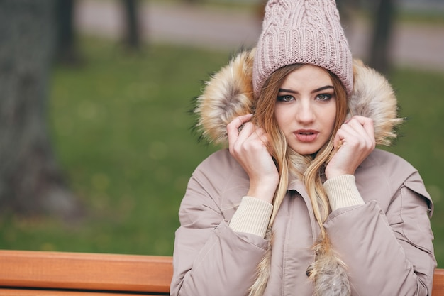 Młoda atrakcyjna kobieta w jesiennych ubraniach siedzi na ławce w parku miejskim