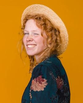 Młoda atrakcyjna kobieta w kapeluszu mrugając na kamery
