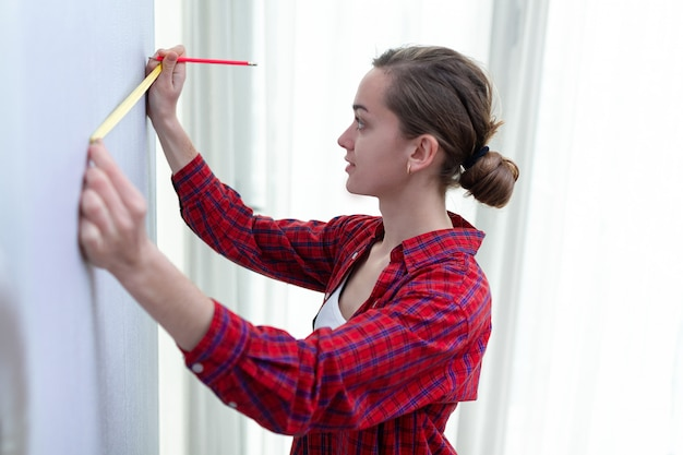 Młoda atrakcyjna kobieta w koszulce bierze udział w naprawach domowych i mierzy długość ściany za pomocą taśmy mierniczej