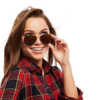 Młoda atrakcyjna kobieta w koszuli i okularach przeciwsłonecznych
