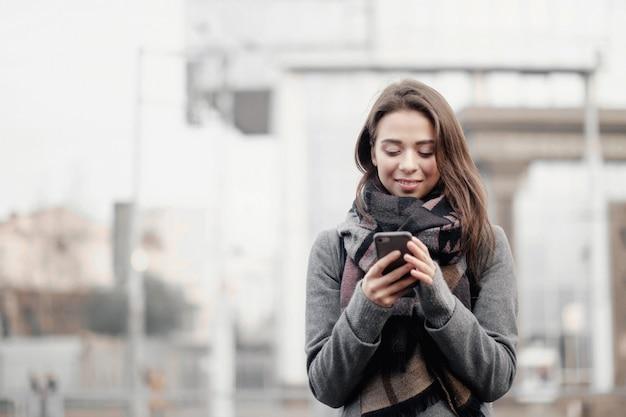 Młoda atrakcyjna kobieta w mieście trzyma telefon w dłoniach