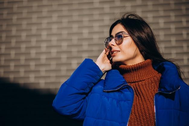 Młoda atrakcyjna kobieta w niebieskiej kurtce zimowej