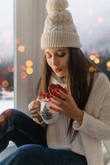Młoda atrakcyjna kobieta w stylowy biały sweter z dzianiny, szalik i czapka siedzi w domu na parapecie na boże narodzenie trzymając kubek pije gorącą herbatę, zimowy las w tle, światła bokeh