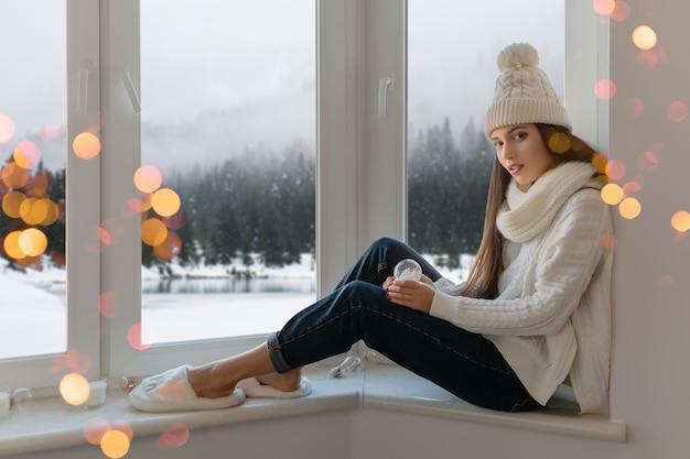 Młoda atrakcyjna kobieta w stylowym białym swetrze z dzianiny, szaliku i czapce siedzi w domu na parapecie na boże narodzenie trzymając szklaną kulę śnieżną obecną dekorację, zimowy widok na las, światła bokeh