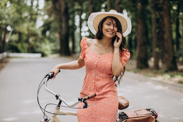 Młoda atrakcyjna kobieta w sukni jazdy na rowerze i korzystania z telefonu