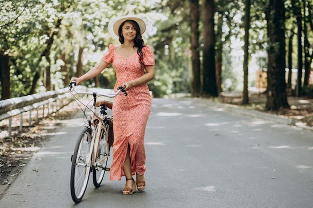 Młoda atrakcyjna kobieta w sukni jazdy na rowerze