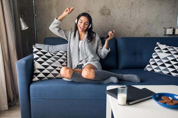 Młoda atrakcyjna kobieta w swobodnym stroju relaks w domu, czas wolny, zabawa, uśmiechanie się słuchanie muzyki na słuchawkach, taniec siedzący na kanapie, wesoły, szczęśliwy, w pończochach, sweter