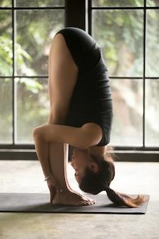 Młoda atrakcyjna kobieta w uttanasana ćwiczeniu, pracowniany tło