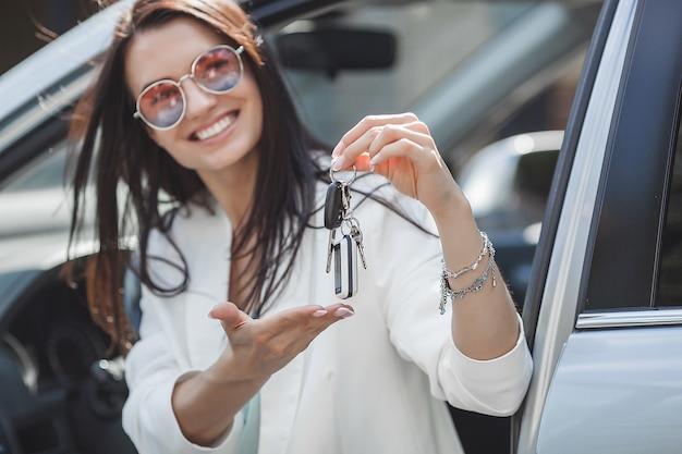 Młoda atrakcyjna kobieta właśnie kupiła nowy samochód. kobieta trzyma klucze od nowego samochodu.