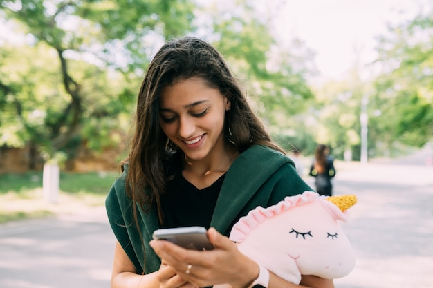 Młoda atrakcyjna kobieta wpisywanie wiadomości na jej telefon komórkowy.