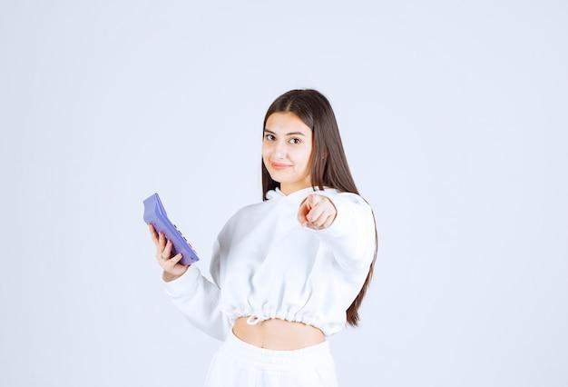 Młoda atrakcyjna kobieta wskazuje na kamerę z elektronicznym kalkulatorem.