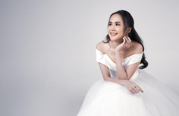 Młoda atrakcyjna kobieta z azji, wkrótce narzeczona, ubrana w białą suknię ślubną, siadając, wyglądając na szczęśliwą. koncepcja fotografii przedślubnej.