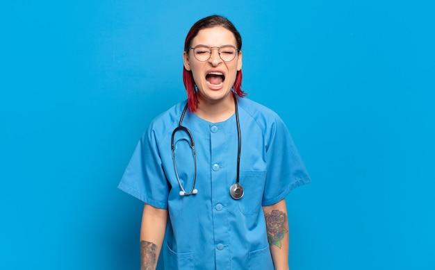 Młoda atrakcyjna kobieta z czerwonymi włosami agresywnie krzycząca, wyglądająca na bardzo wściekłą, sfrustrowaną, oburzoną lub zirytowaną, wrzeszczącą nie. koncepcja pielęgniarki szpitalnej