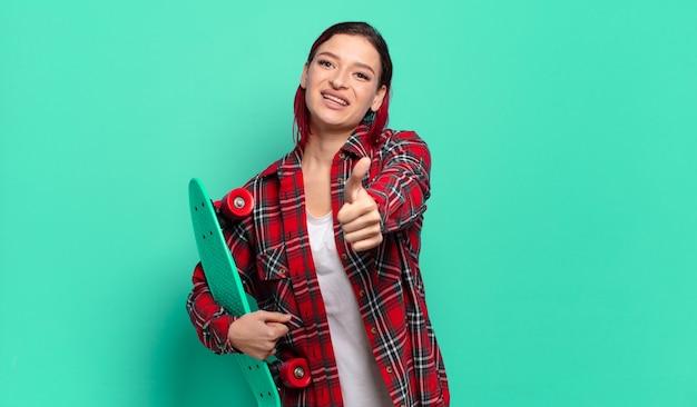 Młoda atrakcyjna kobieta z czerwonymi włosami czuje się dumna, beztroska, pewna siebie i szczęśliwa, uśmiecha się pozytywnie z kciukami do góry i trzyma deskorolkę