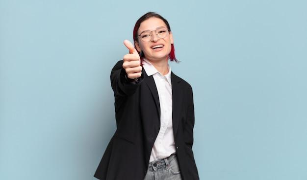 Młoda atrakcyjna kobieta z czerwonymi włosami czuje się dumna, beztroska, pewna siebie i szczęśliwa, uśmiecha się pozytywnie z kciukami do góry