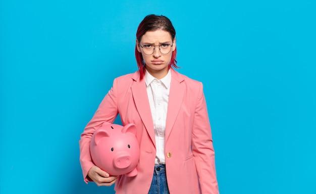 Młoda atrakcyjna kobieta z czerwonymi włosami czuje się smutna i jęcząca z nieszczęśliwym spojrzeniem, płacze z negatywnym i sfrustrowanym nastawieniem. humorystyczny pomysł na biznes.