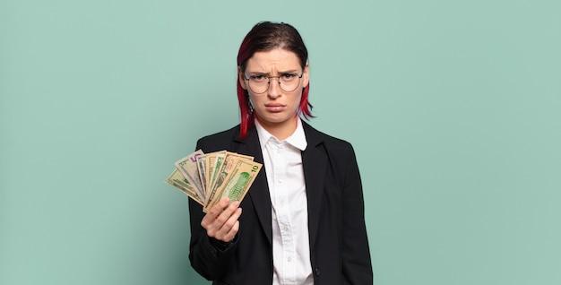 Młoda atrakcyjna kobieta z czerwonymi włosami czuje się smutna i jęcząca z nieszczęśliwym spojrzeniem, płacze z negatywnym i sfrustrowanym nastawieniem. koncepcja pieniędzy