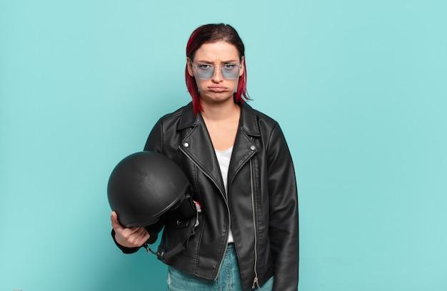 Młoda atrakcyjna kobieta z czerwonymi włosami czuje się smutna i jęcząca z nieszczęśliwym spojrzeniem, płacze z negatywnym i sfrustrowanym nastawieniem