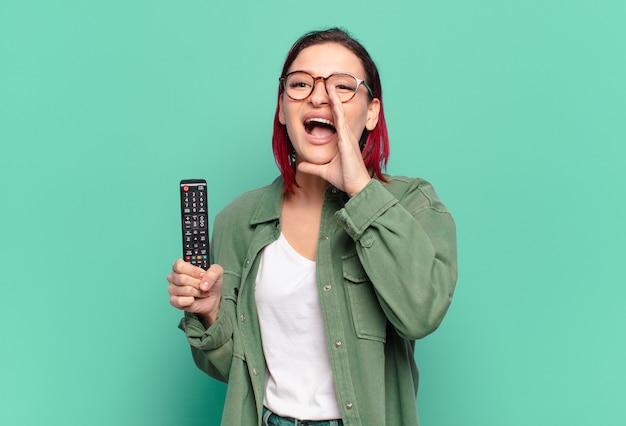 Młoda atrakcyjna kobieta z czerwonymi włosami czuje się szczęśliwa, podekscytowana i pozytywna, krzyczy głośno z rękami obok ust, woła i trzyma pilota do telewizora