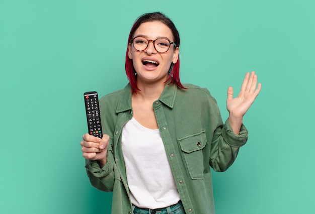 Młoda atrakcyjna kobieta z czerwonymi włosami czuje się szczęśliwa, podekscytowana, zaskoczona lub zszokowana, uśmiechnięta i zdumiona czymś niewiarygodnym i trzyma pilota do telewizora