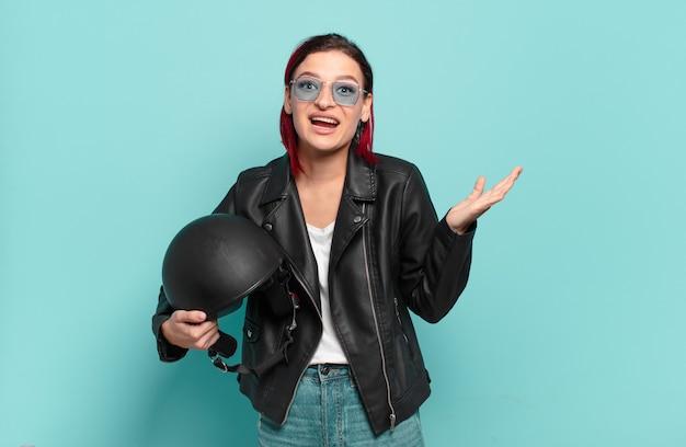 Młoda atrakcyjna kobieta z czerwonymi włosami czuje się szczęśliwa, podekscytowana, zaskoczona lub zszokowana, uśmiechnięta i zdumiona czymś niewiarygodnym. koncepcja motocyklisty